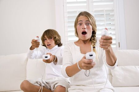 Brother and sister playing video game on white sofa Stock Photo - 6610557