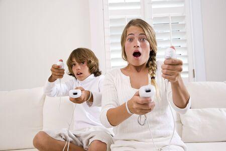 ni�os jugando videojuegos: Hermano y hermana, jugando videojuegos en sof� blanco  Foto de archivo