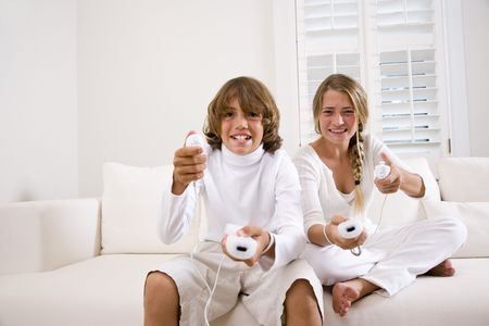 Brother and sister playing video game on white sofa Stock Photo - 6610542