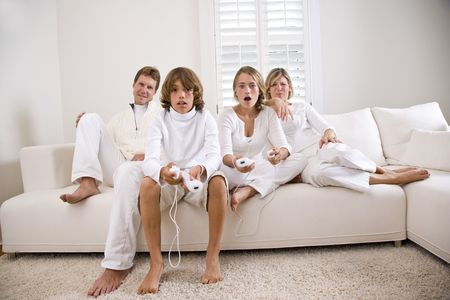 Brother and sister playing video game on white sofa with parents watching