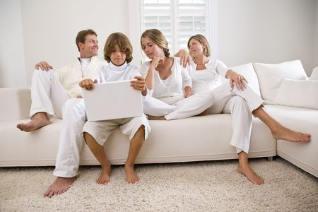 Boy using laptop sitting with family on white sofa Stockfoto