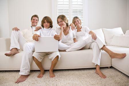 piedi nudi ragazzo: Famiglia rilassante sul divano bianco con il portatile Archivio Fotografico