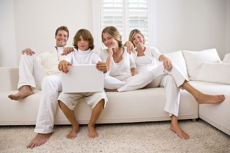Family relaxing on white sofa with laptop photo