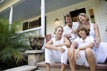 front porch: Familia sentados juntos en pasos de porche delantero