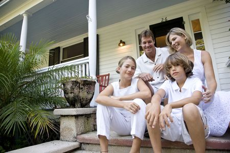 tween boy: Family sitting together on front porch steps Stock Photo