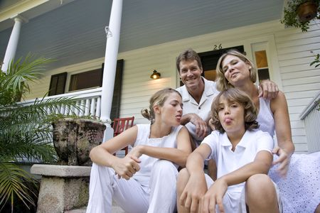 Family sitting together on front porch steps Imagens