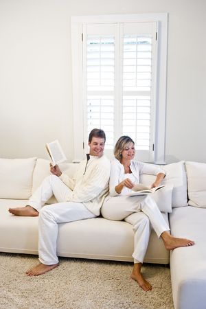 Mid-adult couple relaxing and reading together on white living room sofa 스톡 콘텐츠