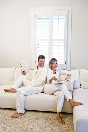 Mid-Adult paar ontspannende en samen lezen op het witte huis kamer sofa