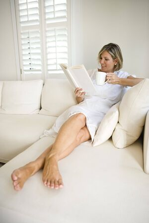 Woman relaxing by window on sofa reading book photo