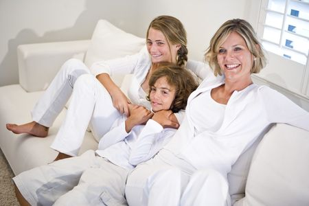 Mother and children relaxing on white sofa photo