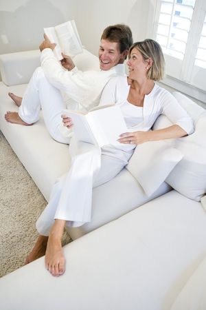 Couple sitting together on white sofa relaxing and reading books photo