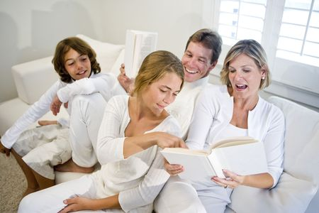 Family sitting on sofa together looking at book mom is reading photo
