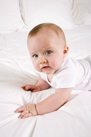 Cute six month old baby on a white bed