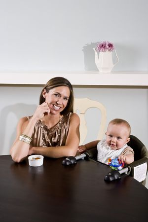 Mother with six month old baby sitting in high chair Stock Photo - 6644289