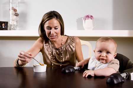 Mother feeding six month old baby sitting in high chair Stock Photo - 6644292