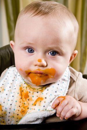 babero: Bebé de seis meses de edad desordenado vistiendo babero después de comer alimentos sólidos