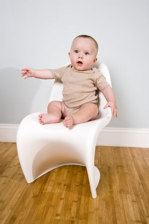 Six month old baby sitting on a chair photo