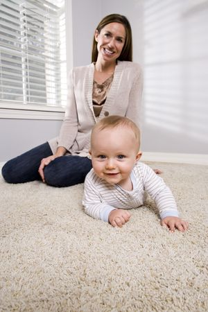 Mother with baby learning to crawl on carpet photo