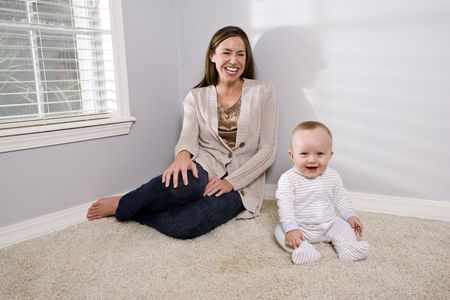 Mother with happy baby sitting on the carpet Stock Photo - 6644329