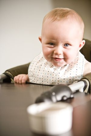 Six month old baby in high chair ready to eat photo