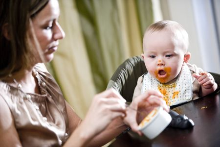 messy: Mother feeding hungry six month old baby solid food Stock Photo