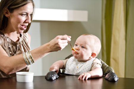 babero: La madre de alimentaci�n de su beb� de seis meses de edad en la silla para beb� Foto de archivo