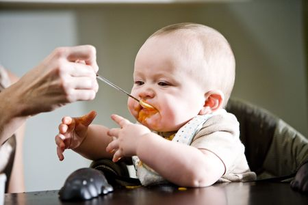 mess: Six month old baby eating solid food from a spoon