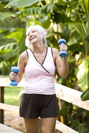 Woman in her 50s staying fit exercising outdoors, walking with dumbbells in her hands photo