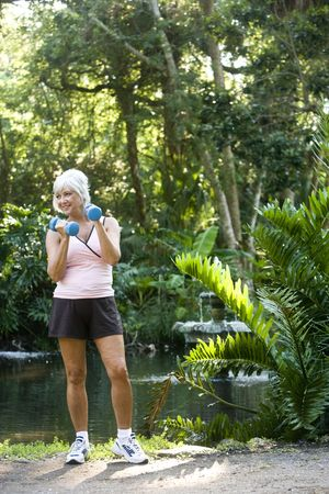 woman, 50s, mature, midlife, exercise, park, nature, fitness, healthy, exercising, weights, workout, hand weight, dumbbells, holding, lifting, strength, training, outdoors, natural, outdoor, fit, female, one person, health, relaxing, peaceful, trees, pond Stock Photo - 6644380