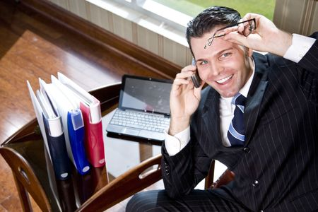 Happy businessman on mobile phone in office, looking up at camera photo