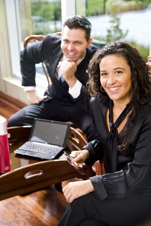 Hispanic businesswoman in office working with male colleague, focus on foreground photo