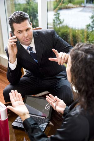 Multitasking businessman in meeting with female Hispanic coworker while listening to mobile phone Stock Photo - 6683467