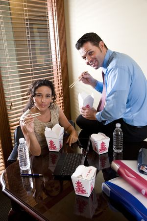 Office workers eating Chinese take-out food in boardroom while working on laptop photo