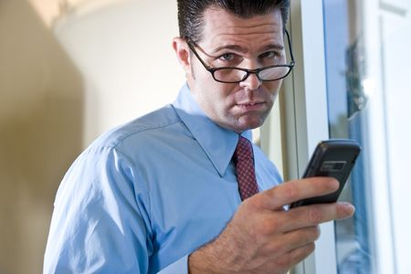 dashing: Serious male business executive sending text message on mobile phone