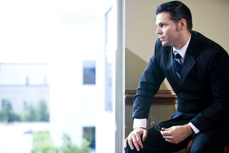 Serious businessman sitting in office looking out window photo