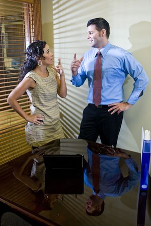 conversing: Female Hispanic office worker and male colleague conversing in boardroom