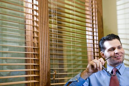 Headshot of confident male office worker sitting by blinds in boardroom Stock Photo - 6683631
