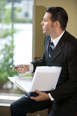 Businessman looking out office window holding binder