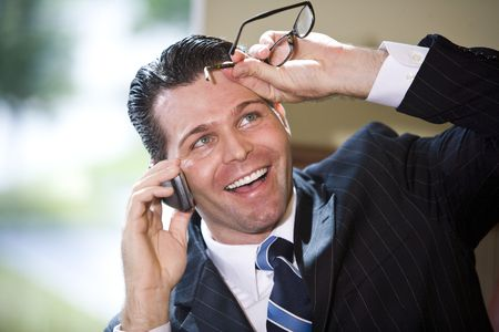 Close up of happy businessman talking on mobile phone, looking up grinning
