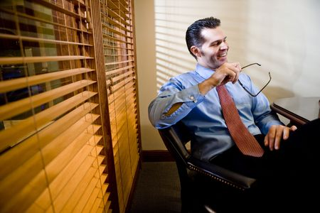 Confident male business executive sitting at boardroom table photo