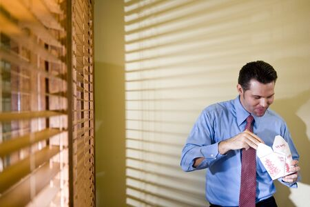 Male office worker eating Chinese take-out in boardroom photo