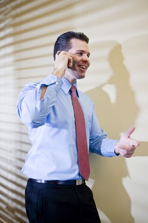Smiling male business executive talking on mobile phone in office photo