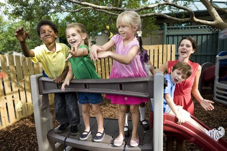 Diverse group of preschool 5 year old children playing in daycare with teacher photo