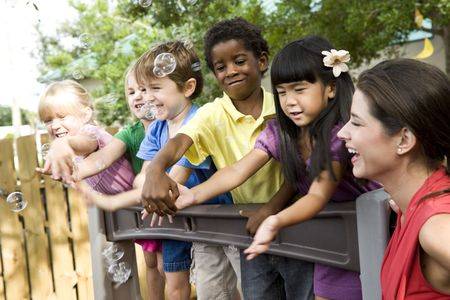 playgroup: Diverse group of preschool 5 year old children playing in daycare with teacher Stock Photo