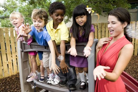 playgrounds: Diverse group of preschool 5 year old children playing in daycare with teacher Stock Photo
