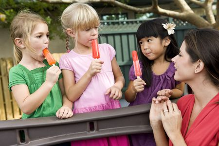Group of preschool 5 year old girls eating popsicles in daycare with teacher Stock Photo