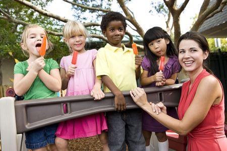 Groep preschool 5 jaar oude meisjes ijslollys eten in kinder opvang met leraar  Stockfoto