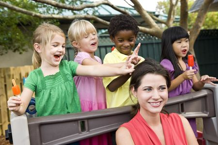 silly: Diverse group of preschool 5 year old children playing in daycare with teacher Stock Photo
