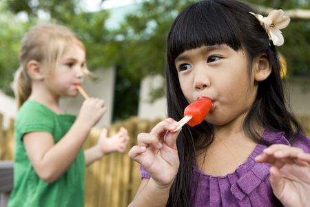 Cute little Asian girl eating a popsicle with friend in background