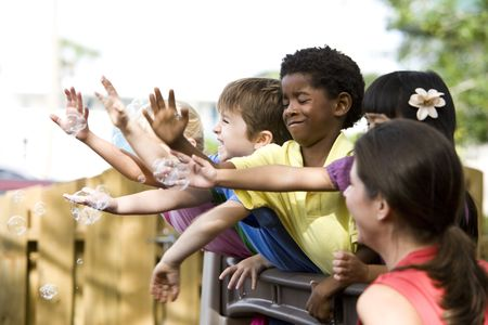 diverse hands: Diverse group of preschool 5 year old children playing in daycare with teacher Stock Photo